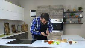 De vette gebaarde mens neemt een foto van voedsel gebruikend een smartphone in een keuken, alvorens een eigengemaakte hamburger t stock video