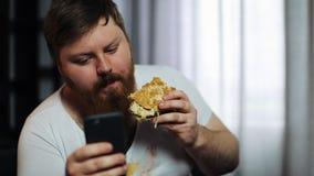 De vette gebaarde mens typt iets in zijn smartphone die een hamburger op de laag eten stock video
