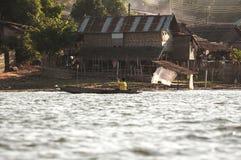 De vette jongen en de oude houten boot paddelen op rivier in Sangkhla Buri, Kanchanaburi-provincie Stock Afbeeldingen