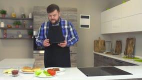 De vette Kaukasische mens met een baard in een schort en met een tablet controleert de ingrediënten het maken van hamburger, snel stock footage