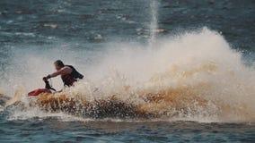 De vette kerel in reddingsvest die straalski berijden op meerwater, het maken draait en springt stock footage