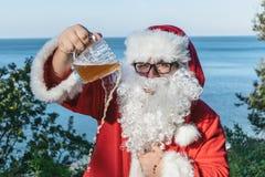 De vette mens in glazen kleedde zich aangezien de Kerstman bier van een mok aan de grond giet Kerstman tegen dronkenschap stock foto