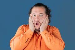 De vette mens in oranje overhemd houdt zijn handen over zijn gezicht Hij is zeer verrast stock afbeeldingen