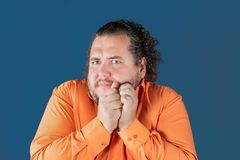 De vette mens in oranje overhemd houdt zijn handen over zijn gezicht op blauwe achtergrond Hij is zeer verrast royalty-vrije stock afbeeldingen