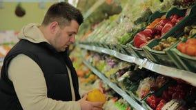 De vette mens in de supermarkt kiest fruit voor zich stock videobeelden