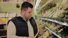 De vette mens in de supermarkt kiest fruit voor zich stock video