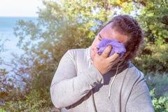 De vette mens veegt zijn gezicht met een handdoek af die zich op de oceaan bevinden sport en een gezonde levensstijl stock fotografie