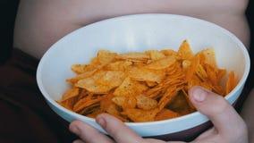 De vette tiener met vette vouwen op zijn lichaam eet chips Ongezond voedsel, snel voedsel Het probleem van de kinderen` s voeding stock videobeelden