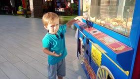 de video van weinig peuterjongen die met muntstuk spelen stelde machine bij pretpark in werking Kind die zacht stuk speelgoed pro stock footage