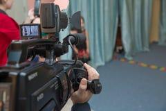 De Videocameraexploitant die van de handcontrole camcorder met zijn materiaal openlucht met vage achtergrond werken Sluit omhoog  stock foto