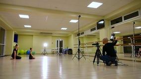 De videocameramanfilm als twee slanke leuke artistieke turners van meisjeszusters in zwarte sportkleding maakt opwarming in gymna stock footage