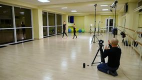 De videocameramanfilm als twee slanke leuke artistieke turners van meisjeszusters in zwarte sportkleding maakt opwarming in gymna stock videobeelden