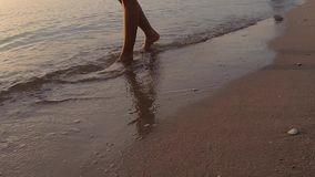 De videolengte, Vrouwenbenen op het strand schuurt golvenoverzees bij zonsopgang stock videobeelden
