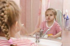 De vier-jaar-oude tanden van de meisjesspoeling na het schoonmaken in de badkamers stock fotografie