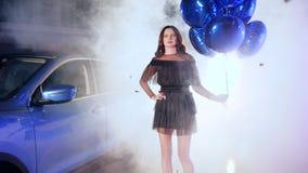 De viering, schitterend brunette met opblaasbare ballons bevindt zich dichtbij voertuig in mist onder vliegend klatergoud stock video