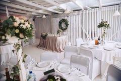 De viering van het huwelijk Banket met decorateurs wordt verfraaid die Bloemsamenstellingen en lijsten voor gasten met decor Stock Foto