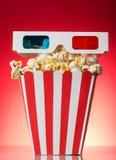 De vierkante gestreepte doos met popcorn en 3D glazen op een rood Royalty-vrije Stock Foto's