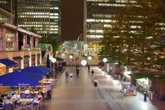 De vierkante mening van Canary Wharf in nachtlichten met beambten die uit na werkdag in lokale koffie en bars koelen Stock Foto's