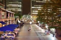 De vierkante mening van Canary Wharf in nachtlichten met beambten die uit na werkdag in lokale koffie en bars koelen Royalty-vrije Stock Fotografie