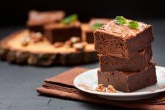 De vierkante stukken van de chocoladebrownie in stapel op witte die plaat met okkernoten, met muntbladeren en cacao op zwarte ach Stock Fotografie