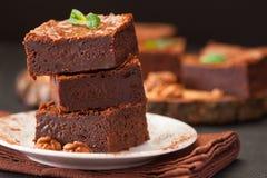 De vierkante stukken van de chocoladebrownie in stapel op witte die plaat met okkernoten, met muntbladeren en cacao op zwarte ach Stock Foto