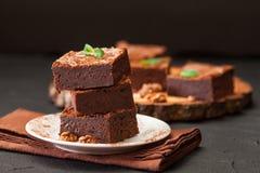 De vierkante stukken van de chocoladebrownie in stapel op witte die plaat met okkernoten, met muntbladeren en cacao op zwarte ach Stock Foto's