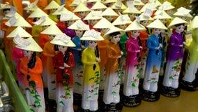 De Vietnamese beeldjes van vrouwenchina, die traditionele vrouwelijke kleding, voor verkoop in Saigon-markt, Vietnam dragen stock footage