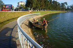 De Vietnamese hygiënearbeider neemt vuilnis van meer op Royalty-vrije Stock Foto's
