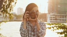 De Vietnamese meisjesfotograaf neemt beelden van aard in het stadscentrum bij zonsondergang stock videobeelden