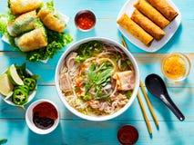 De Vietnamese soep van phobo met voorgerechten op lijst en gemotregend met srirachasaus stock afbeeldingen