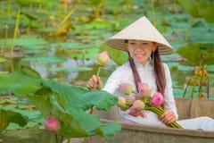 De Vietnamese vrouwen verzamelen de lotusbloem stock afbeelding
