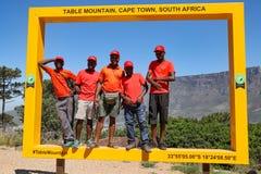 De vijf het glimlachen kerels in rood nemen een foto in geel groot kader op Signaalheuvel in Cape Town met Lijstberg op de achter royalty-vrije stock fotografie