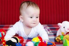 de vijf-maanden baby ligt op een bank onder speelgoed Stock Fotografie