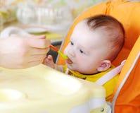 De vijf-maanden baby wordt gevoed door puree Royalty-vrije Stock Fotografie