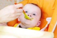 De vijf-maanden baby wordt gevoed door puree van een lepel Stock Foto's