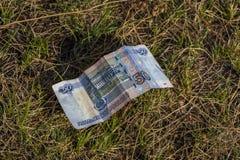 De vijftig roebelsrekening ligt op de grond of het gras Het concept financieel verlies Stock Foto's