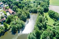 De vijver bij moated kasteel Neuhaus van de lucht, met struiken en bomen, bij de rand van het dorp stock foto