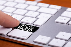 De vinger die op sleutel drukken met bidt voor het teken van Parijs Royalty-vrije Stock Fotografie