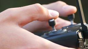 De vinger drukt de knopen op ver van quadrocopter of de hommel dichte omhooggaande mening stock videobeelden
