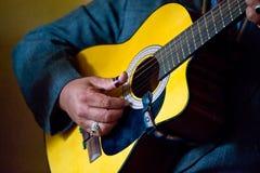 De vinger van de persoon het plukken gitaar stock fotografie