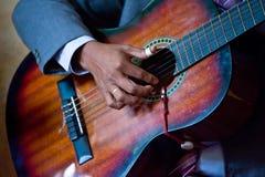 De vinger van de persoon het plukken gitaar stock foto