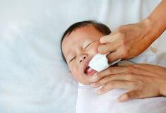 De vinger van het moedergebruik om tong en melktanden met schoon gaas schoon te maken stock afbeeldingen