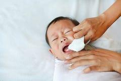 De vinger van het moedergebruik om tong en melktanden met schoon gaas schoon te maken stock afbeelding