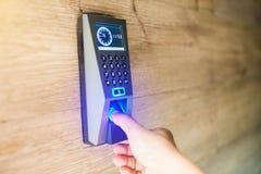 De vinger van de mensenduw neer op de elektronische controlemachine om tot de deur toegang te hebben stock afbeelding