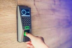 De vinger van de mensenduw neer op de elektronische controlemachine om tot de deur toegang te hebben stock afbeeldingen