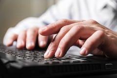 De vingers van de close-upmens op een computertoetsenbord Stock Foto's