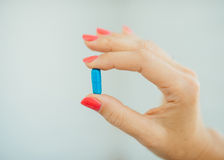 De vingers van vrouwen met roze manicure die blauw vergen royalty-vrije stock foto
