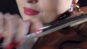 De violist houdt een boog in haar hand en speelt Zwarte achtergrond Sluit omhoog stock footage