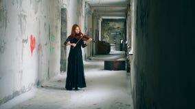 De violist speelt instrument in een lege gang van de verlaten bouw stock videobeelden