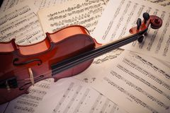 De viool ligt op verspreide nota's stock afbeeldingen